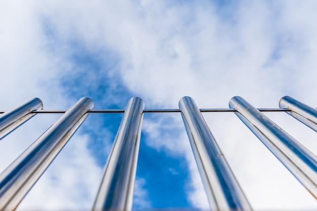 Cerca com barras altas de metal apontando para o céu azul com perspectiva vista de baixo.