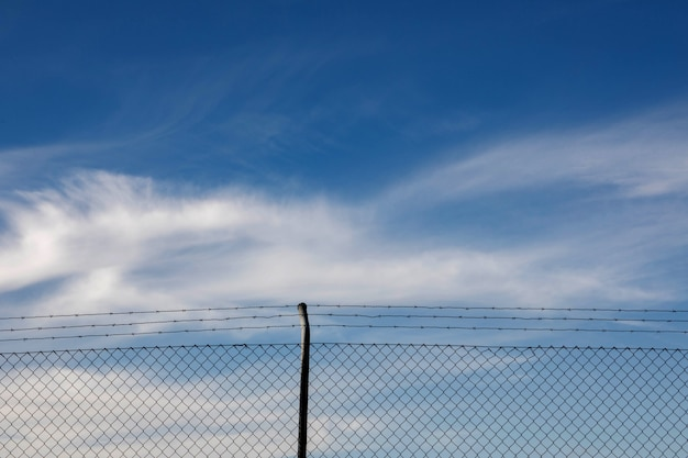 Cerca de arame com um céu azul com nuvens