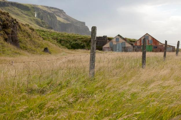 Cerca de arame farpado e fenceposts em um pasto com celeiros e montanhas