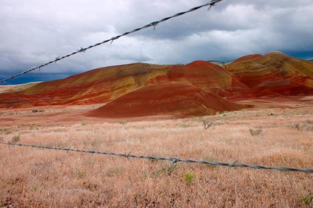 Cerca de arame farpado por terra estéril e colinas