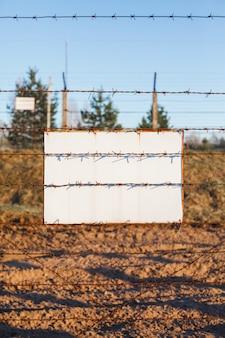 Cerca de arame farpado protege a zona de perigo. placa de sinal branco