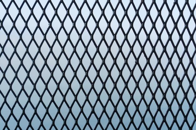 Cerca de ferro ou rede de metal sobre fundo azul