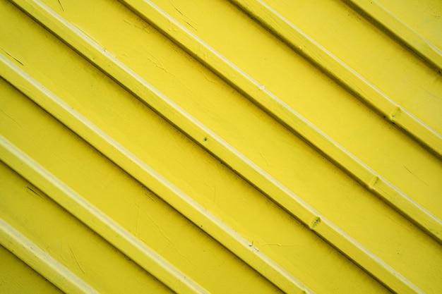 Cerca de lata de ferro amarelo forrado de fundo. textura de metal