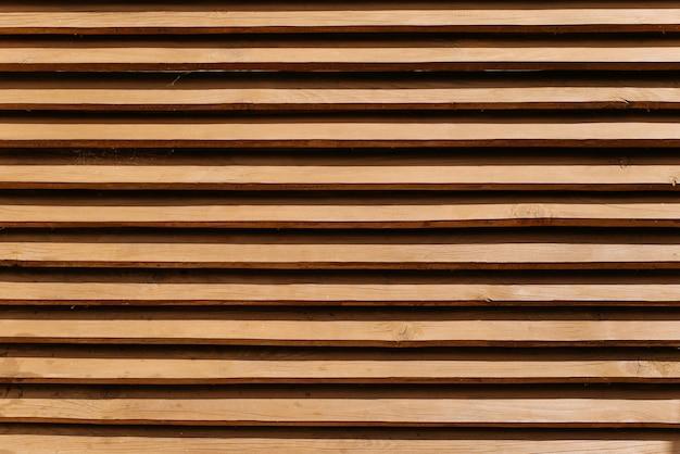 Cerca de madeira feita de tábuas finas horizontais. fundo de cerca marrom texturizado, padrão de painéis de madeira, ao ar livre