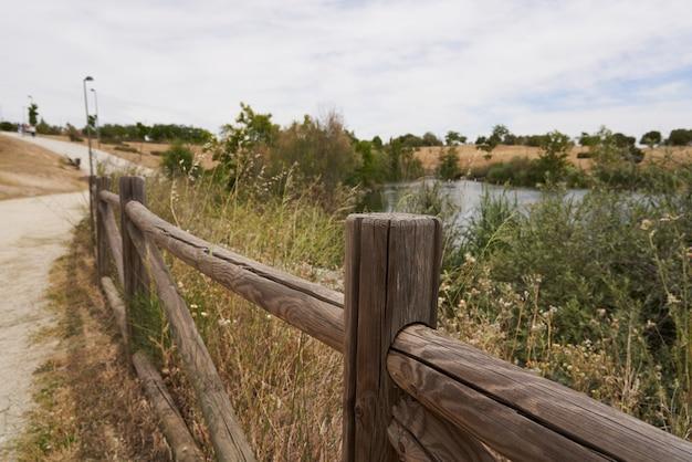 Cerca de madeira marrom com um lago ao fundo em um caminho de parque