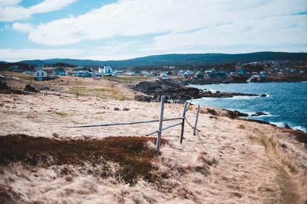 Cerca de madeira marrom na areia marrom perto do corpo de água durante o dia