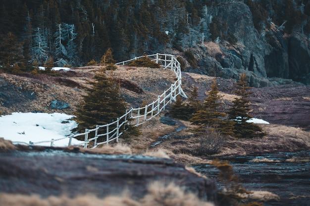 Cerca de madeira marrom na montanha rochosa marrom durante o dia