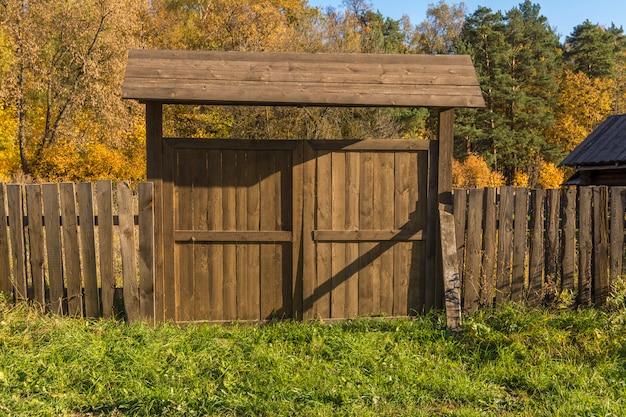 Cerca de madeira na aldeia. portão de madeira velha.