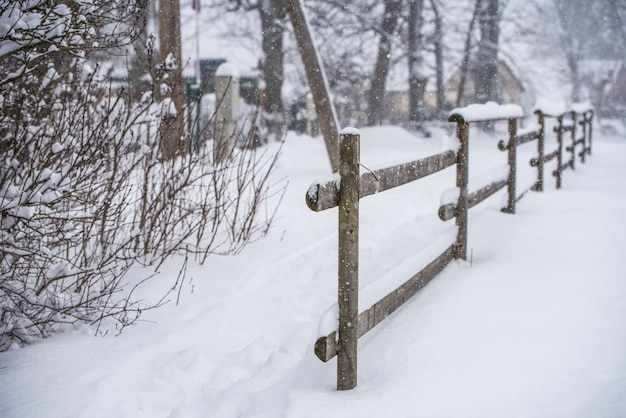 Cerca de madeira na neve no fundo do país de inverno.