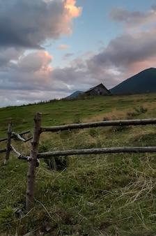 Cerca de madeira perto de uma casa nas montanhas contra o céu com nuvens e montanhas