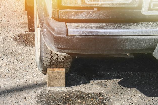Cerca de madeira sob a roda para a máquina. parada de roda.