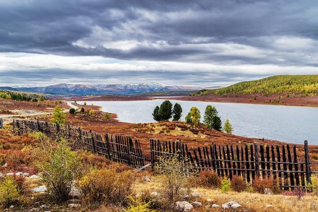 Cerca de madeira velha de paisagem montanhosa de outono na margem do lago uzunkel altai rússia