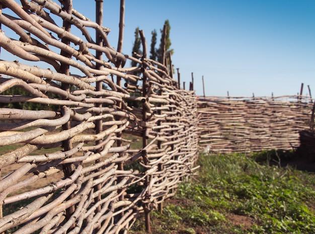 Cerca de vime feita de madeira flexível (salgueiro ou avelã). a textura do tronco de uma árvore natural. o conceito de vida suburbana.