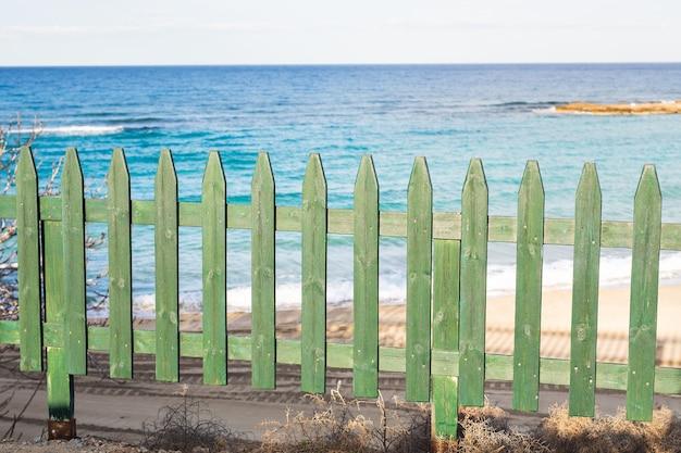 Cerca decorativa pequena de madeira verde na praia.