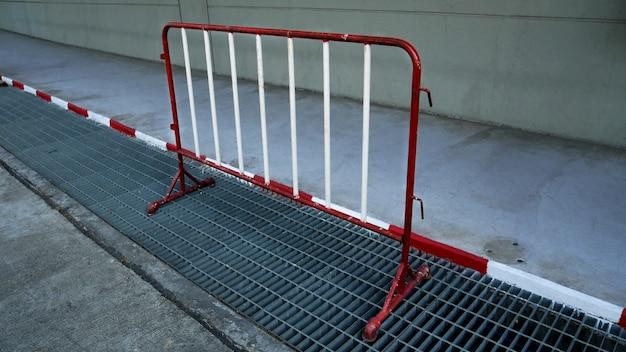 Cerca portátil portátil pintada de vermelho e branco perto de calçada e grade de aço