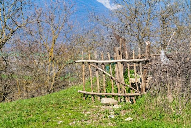 Cerca velha de varas de madeira perto da fazenda