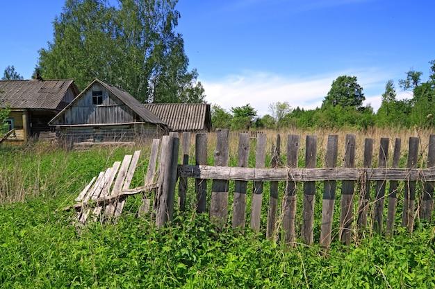 Cerca velha perto de edifício de madeira rural