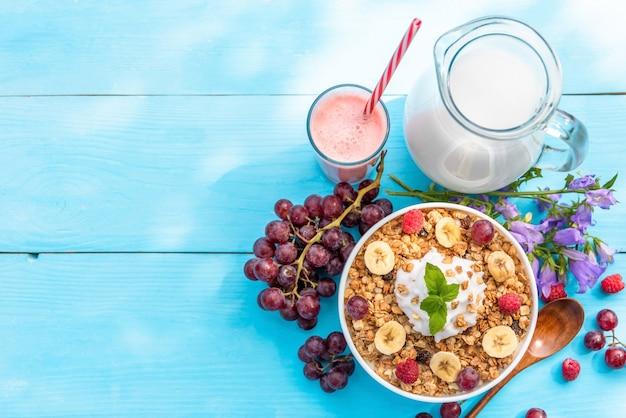 Cereais ao ar livre do pequeno-almoço de verão com framboesas, banana e uvas.