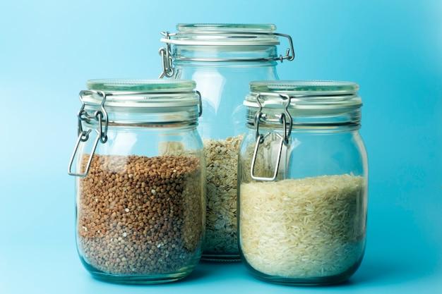 Cereais (aveia, trigo sarraceno, arroz) em potes de vidro na cozinha. conceito sem glúten. variedades de cereais para fazer refeições e alimentos caseiros saudáveis.