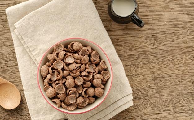 Cereais café da manhã sabor cacau em tigela no pano de fundo de madeira com espaço de cópia, vista superior
