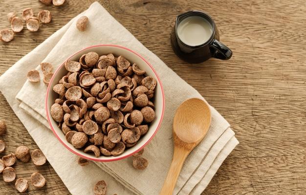 Cereais café da manhã sabor cacau em tigela no pano de fundo de madeira com espaço de cópia