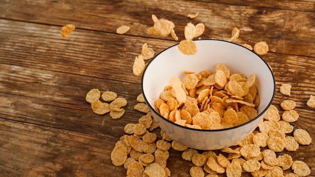 Cereais caindo em uma tigela branca sobre uma mesa de madeira. foto brilhante. pequeno-almoço saudável rápido