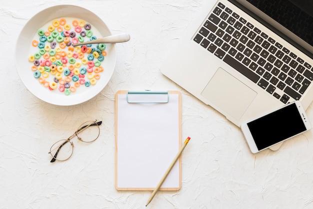 Cereais coloridos com tigela de leite e laptop no plano de fundo texturizado