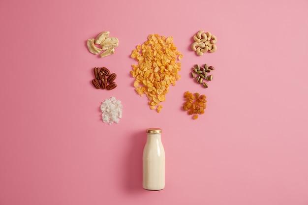 Cereais com maçãs secas, tâmaras, caju, pistache em volta da garrafa com leite