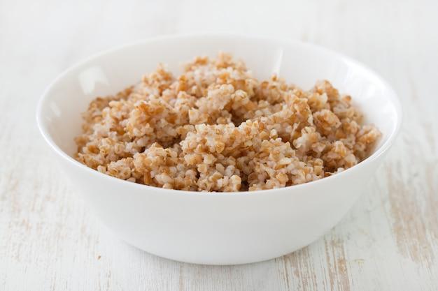 Cereais cozidos em tigela branca na superfície de madeira branca