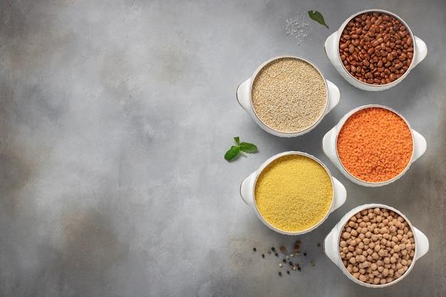 Cereais crus diferentes: cuscuz, feijão, quinoa, lentilhas, especiarias do grão de bico, ervas, espaço para cópia de sal, vista superior,