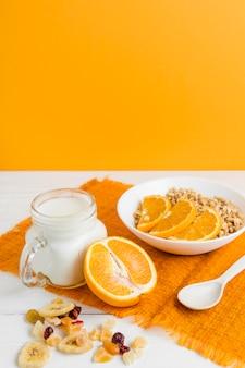 Cereais de alto ângulo com laranja e iogurte