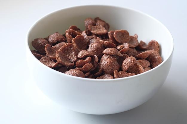 Cereais de café da manhã de chocolate em uma tigela branca na mesa.
