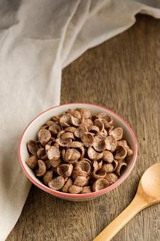 Cereais de café da manhã sabor cacau em tigela na mesa de madeira