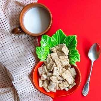 Cereais de cereal no café da manhã em uma tigela e um copo de leite no vermelho