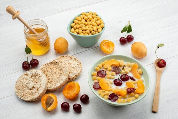 Cereais de frente para o leite dentro do prato com biscoitos, frutas e mel na mesa branca bebem leite com leite.