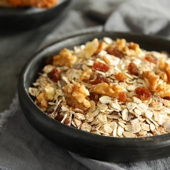 Cereais de granola caseira saudável com nozes e passas em fundo cinza