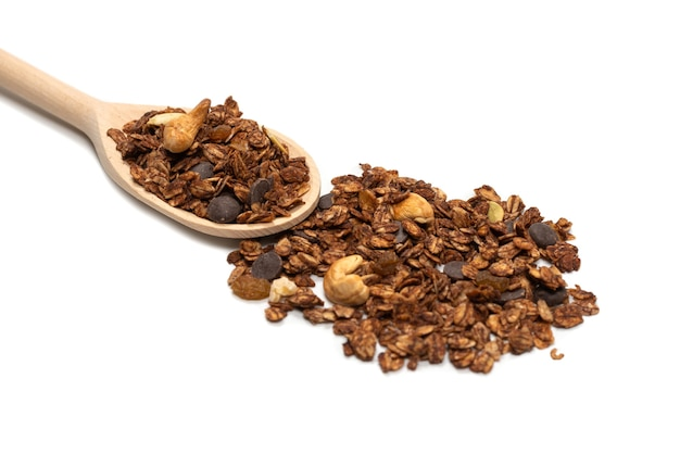 Cereais de granola de chocolate com nozes em uma colher de pau. isolado no branco.