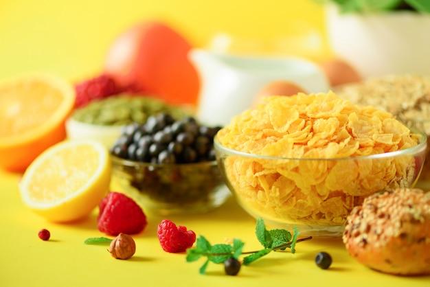 Cereais de milho, muesli, leite, frutas, suco de laranja, iogurte, ovo cozido, nozes, frutas, banana, pêssego no café da manhã. conceito vegan e vegetariano.