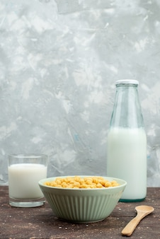Cereais de vista frontal amarelo dentro da placa com leite frio fresco em branco, alimentos de cereais de cereais de pequeno-almoço
