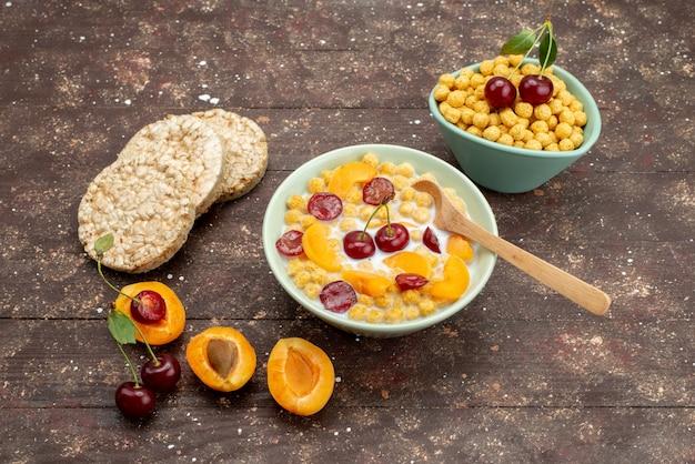 Cereais de vista frontal com leite dentro do prato com biscoitos e frutas no fundo de madeira marrom bebem leite leiteiro