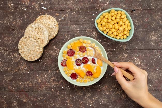 Cereais de vista superior com leite dentro da placa com bolachas no marrom, bebem leite cremoso de leite