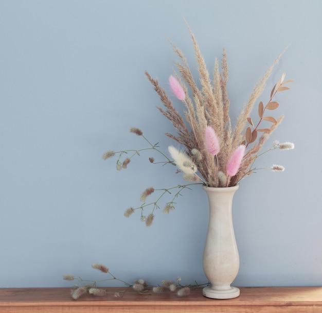 Cereais decorativos secos em vaso em prateleira de madeira