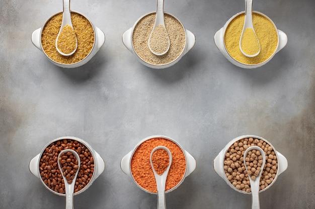 Cereais diferentes em tigelas (cuscuz, feijão, quinoa, bulgur, lentilhas, grão de bico) alimentos saudáveis,