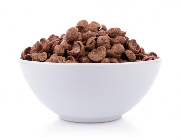 Cereais do chocolate na bacia branca no fundo branco. flocos de milho