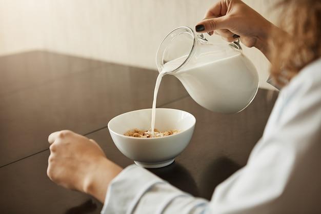 Cereais é o melhor café da manhã para manter a forma. foto recortada de mulher sentada em roupa de noite, derramando leite na tigela com cereais, preparando a refeição para comer e correu para o trabalho, ouvindo notícias na tv
