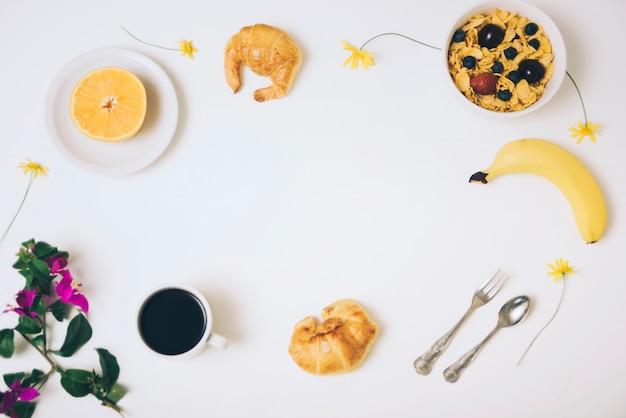 Cereais em flocos de milho; banana; croissants; metade de laranja e xícara de café com flor de buganvílias em pano de fundo branco