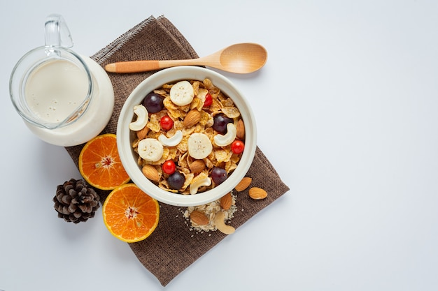 Cereais em uma tigela e frutas misturadas no fundo de mármore