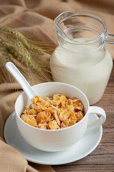 Cereais em uma tigela e leite em fundo escuro de madeira