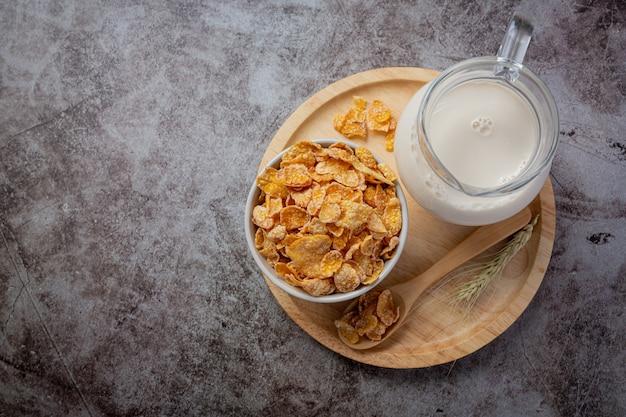 Cereais em uma tigela e leite em fundo escuro