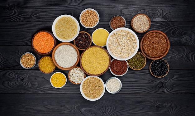Cereais, grãos, sementes e grumos na superfície de madeira preta